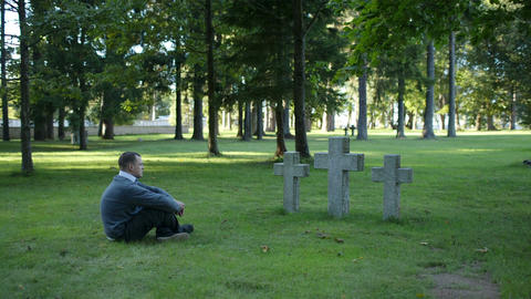 Man Sitting Mourning In Front Of Three Crosses stock footage