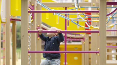 Cute little boy climbing on a jungle gym Stock Video Footage