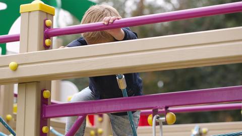 Boy on playground equipment Footage