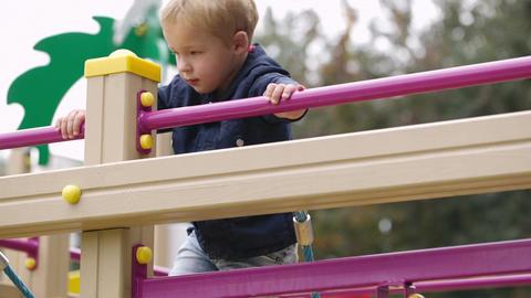 Boy on playground equipment Stock Video Footage