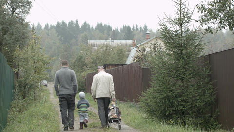 Two men and a boy walking in the countryside Footage