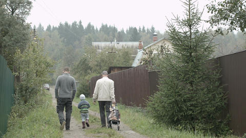 Two men and a boy walking in the countryside Stock Video Footage