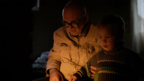 Grandfather and grandson near fire at home Stock Video Footage
