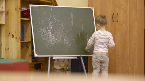 Little boy drawing on a chalkboard at kindergarten Stock Video Footage