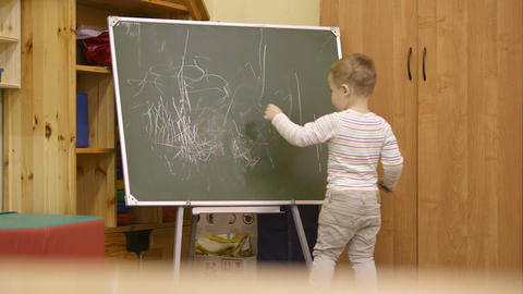 Little boy drawing on a chalkboard at kindergarten Footage