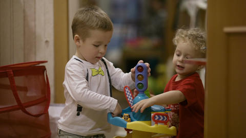 Two young children playing with their toys Stock Video Footage