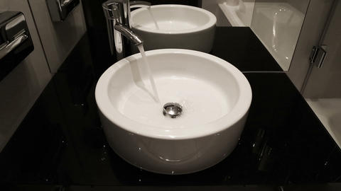 water flows from tap into modern sink Stock Video Footage