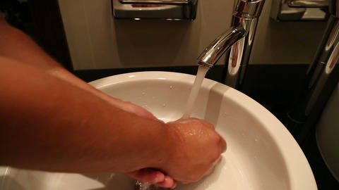 man washes his hands under tap Stock Video Footage