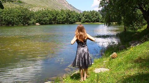 Young beautiful girl in a dress dances on the shor Stock Video Footage
