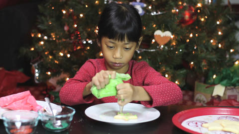 Asian Girl Adds Icing To Christmas Cookie Footage