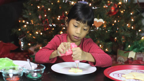 Asian Girl Adds Icing To Christmas Cookie Stock Video Footage