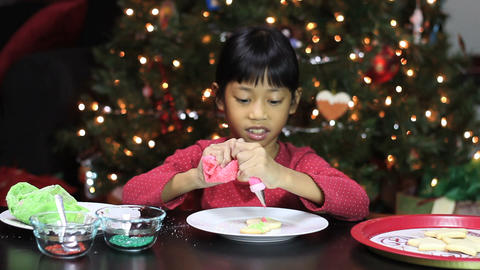 Asian Girl Adds Icing To Snowman Christmas Cookie Stock Video Footage