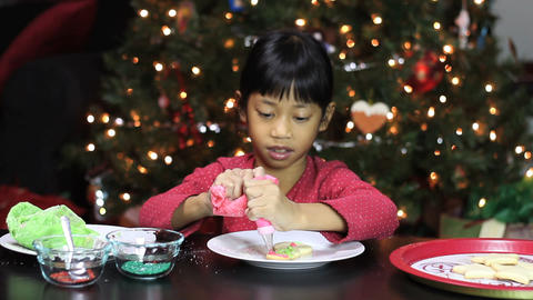 Asian Girl Adds Icing To Snowman Christmas Cookie Footage
