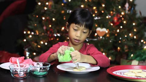 Asian Girl Decorates Snowman Christmas Cookie Stock Video Footage