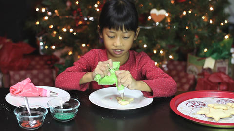 Girl Adds Green Icing To Bell Christmas Cookie Footage