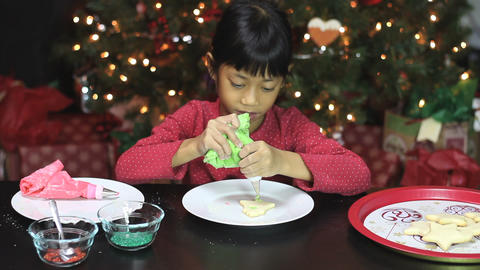 Girl Adds Green Icing To Bell Christmas Cookie Stock Video Footage