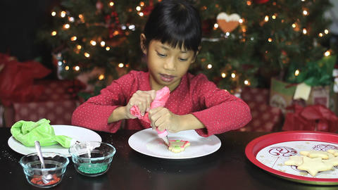 Girl Adds Red Icing To Bell Christmas Cookie Stock Video Footage