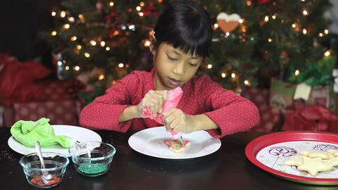 Girl Adds Red Icing To Bell Christmas Cookie Footage