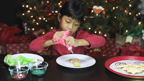 Girl Adds Red Icing To Snowman Christmas Cookie Stock Video Footage