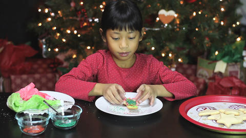 Girl Adds Red Icing To Snowman Christmas Cookie Footage