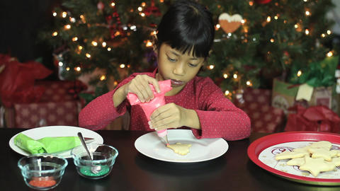 Girl Decorating Bell Shaped Christmas Cookie Footage
