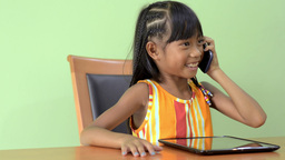 Young Asian Girl Answers Her Cell Phone While Play stock footage