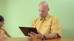 Girl Walks in and Takes iPad from her Father Stock Video Footage