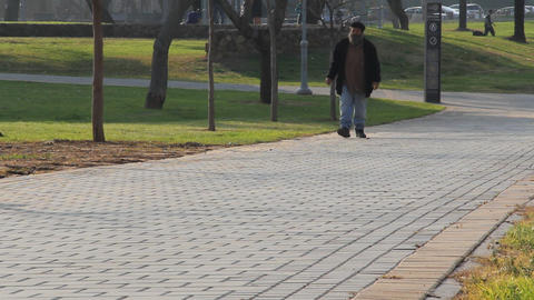 Single man walking in the park Stock Video Footage