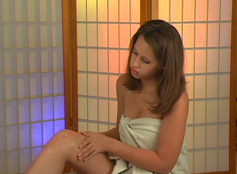 Beautiful Teen Girl Applies Lotion to Her Right Le Footage