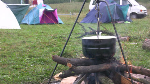 Preparing food in pot above bonfire 3 Footage