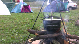 Preparing food in pot above bonfire 3 Stock Video Footage