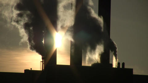 Fumes billow from giant chimney amidt the sunlight (High Definition) Footage