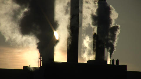 Fumes billow from giant chimney amidt the sunlight (High... Stock Video Footage