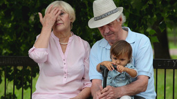 Elderly Couple Sitting With Granddaughter Footage
