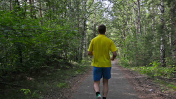 Rear-View Of A Single Runner In The Summer Park Footage