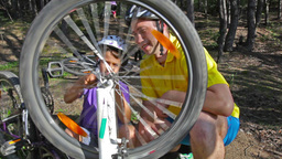 Father And Son Repairing The Bike While Mom Pushing Her Bicycle Away Footage