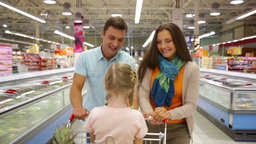 Smiling Parents Pushing A Shopping Trolley With Their Daughter Sitting Inside Footage