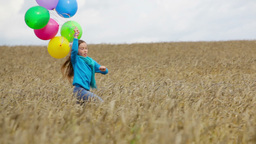 Charming Girl Holding A Bunch Of Colorful Balloons Running In The Countryside Footage