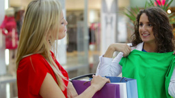 Shopping Lady Showing Her Purchases To Her Friends Trying On A Green Garment Footage