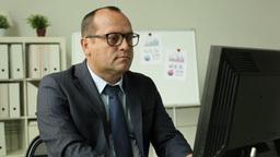 Tilt Of A Mature Entrepreneur Working Behind The Desk In Office Footage