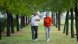Retired Couple Keeping Fit Jogging In The Park Footage