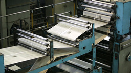 Black-And-White Newspaper Sheets Moving Through Rollers Along The Production Lin Footage