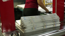 Printing Factory Worker Packing Piles Of Freshly Printed Newspapers With The Hel stock footage