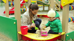 Mother And Daughter Making A Sandpit Together Footage