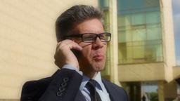 Tilt Down Of A Mature Businessman Calling His Client Footage