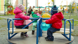 Toddlers Having Fun On A Merry-Go-Round, Their Moms Looking After From Afar Footage
