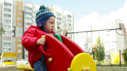 Close-Up Of A Little Boy Rocking On A Playground Swing Piece Footage