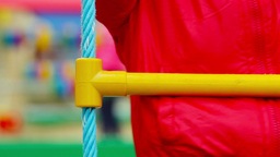 Close-Up Of An Energetic Kid Climbing Up The Rope Ladder Footage