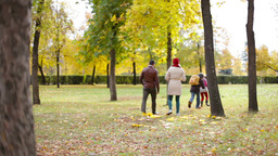 Two Kids Running After Their Parents And Throwing Leaves Upon Them In The Park Footage