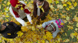 Happy family of four playing with leaves in the park in autumn Footage